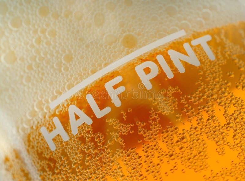 Media medida de la cerveza de la pinta foto de archivo libre de regalías