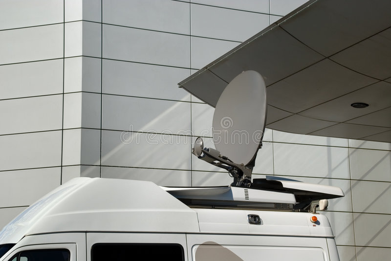 Media mobile satellite dish. Mobile satellite dish on a van or car in an urban environment in front of modern architecture, used by the news media to cover royalty free stock images