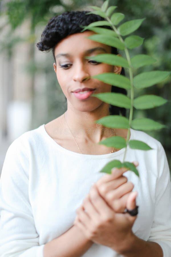 Media muchacha nigeriana americana negra que se coloca con la hoja verde, teniendo blusa blanca de las explosiones y el llevar imágenes de archivo libres de regalías