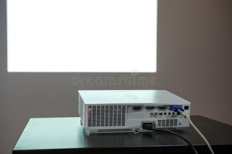 Media projector standing on table, white screen on the wall, nobody. Media projector standing on the table, white screen on the wall, nobody royalty free stock image