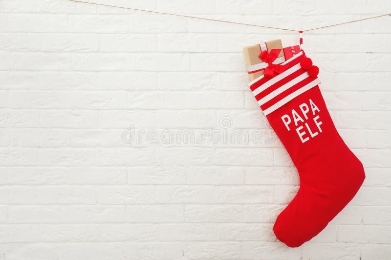 Media roja de la Navidad por completo de los regalos que cuelgan en la pared de ladrillo, espacio para el texto foto de archivo libre de regalías