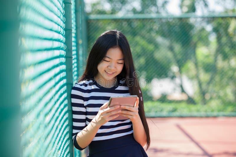 Media sociali della lettura teenager asiatica di età nella felicità della compressa del computer immagine stock