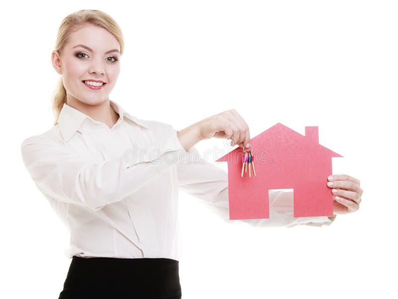 Mediador imobiliário da mulher de negócio que guarda chaves de papel vermelhas da casa fotografia de stock
