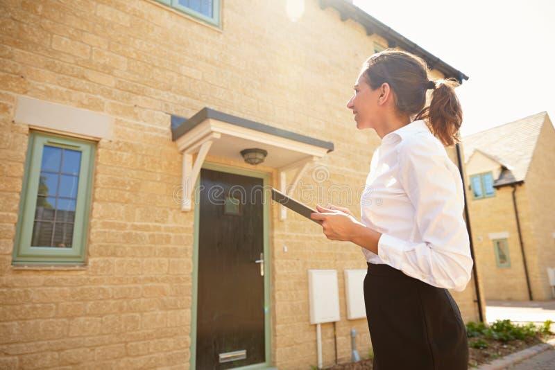 Mediador imobiliário fêmea que olha um exterior da casa fotos de stock royalty free