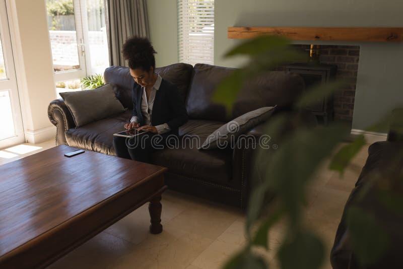Mediador imobiliário fêmea que usa a tabuleta digital na sala de visitas foto de stock