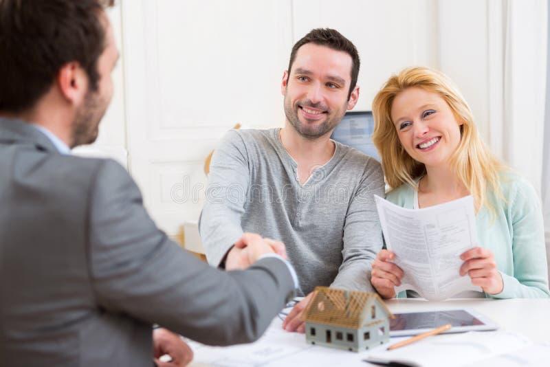 Mediador imobiliário feliz novo do aperto de mão dos pares após ter assinado c fotografia de stock