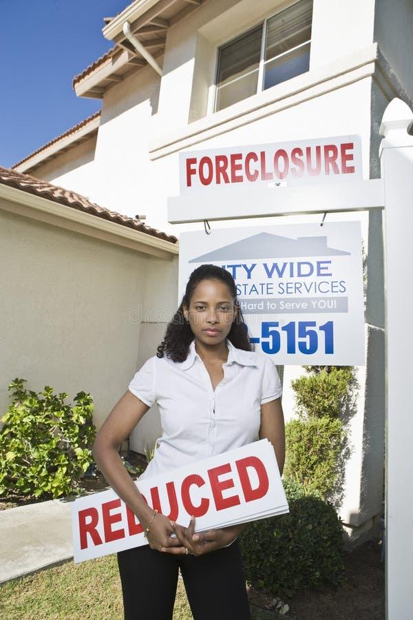 Mediador imobiliário Holding Sign Board fora da casa fotografia de stock royalty free