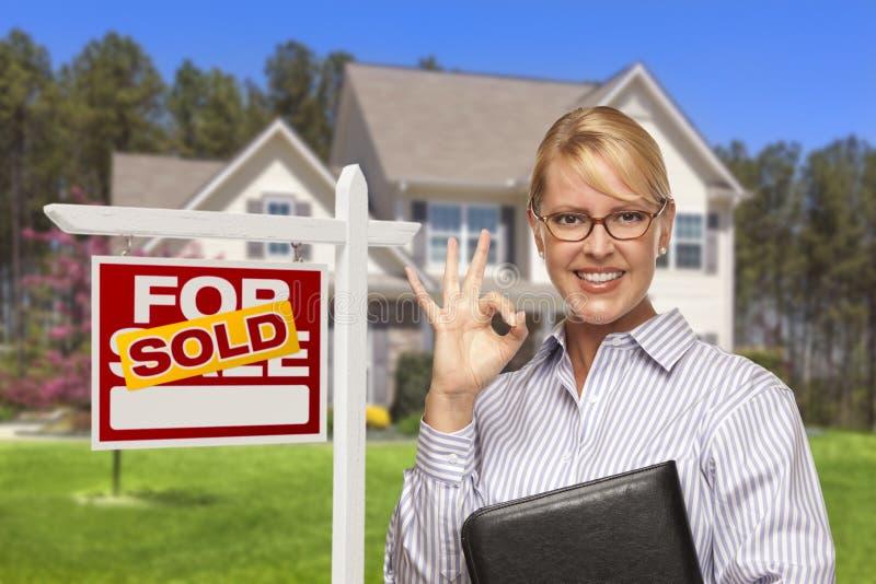 Mediador imobiliário na frente do sinal e da casa vendidos imagens de stock royalty free