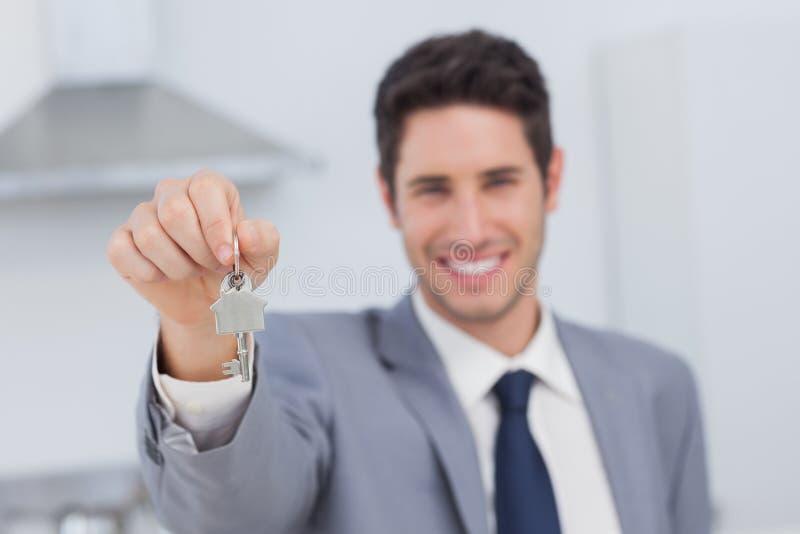 Mediador imobiliário que apresenta a chave da casa imagens de stock royalty free