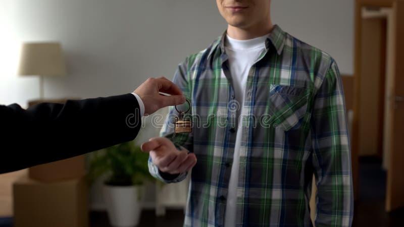 Mediador imobiliário que apresenta a chave da casa nova ao homem novo, creditar da juventude fotografia de stock royalty free