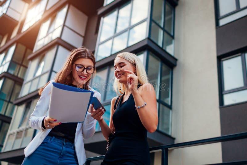 Mediador imobiliário que apresenta o apartamento novo ao cliente A mulher de negócios mostra o contrato ao cliente Riso dos sócio foto de stock