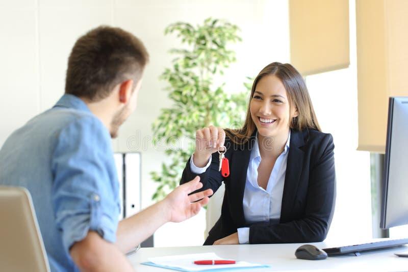 Mediador imobiliário que dá chaves da casa a um cliente imagens de stock