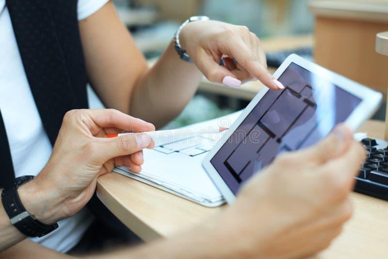 Mediador imobiliário que mostra planos da casa na tabuleta eletrônica fotografia de stock royalty free