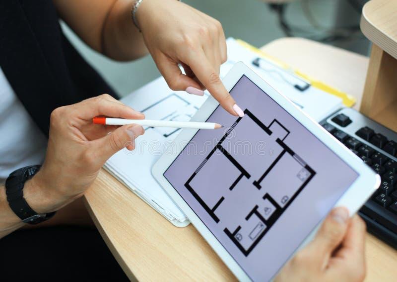 Mediador imobiliário que mostra planos da casa na tabuleta eletrônica imagem de stock royalty free