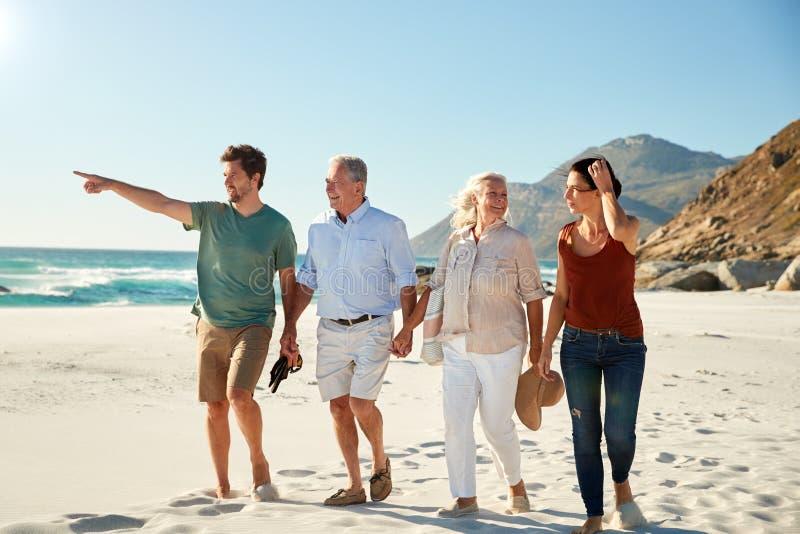 Mediados de adulto y pares blancos mayores que caminan en hablar de la playa junto, integral, cierre para arriba imagen de archivo