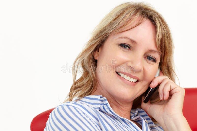 Mediados de empresaria de la edad que usa el teléfono celular imagen de archivo libre de regalías