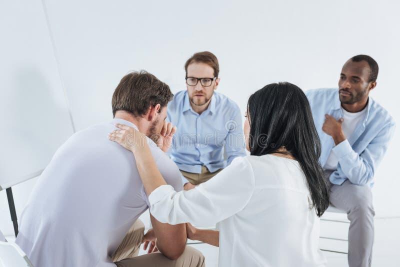 mediados de gente adulta multiétnica que se sienta en sillas y hombre trastornado favorable ilustración del vector