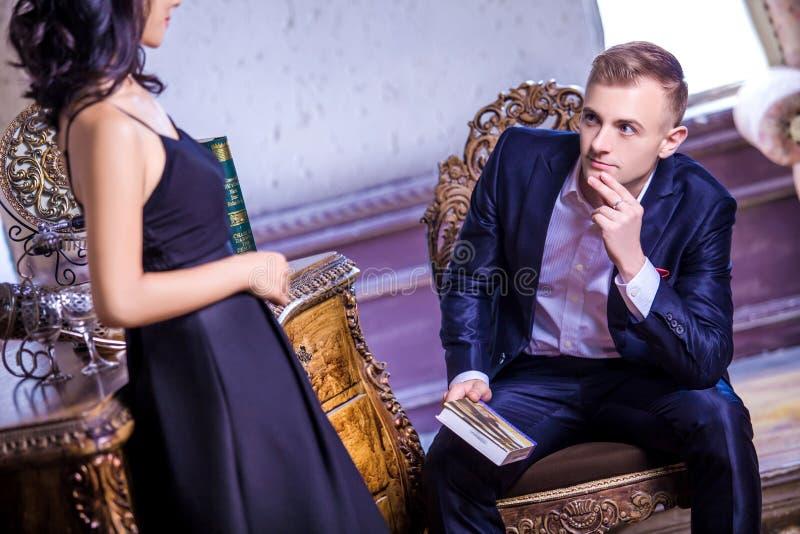 Mediados de hombre adulto cariñoso en el traje que mira a la mujer mientras que se sienta en silla fotos de archivo libres de regalías