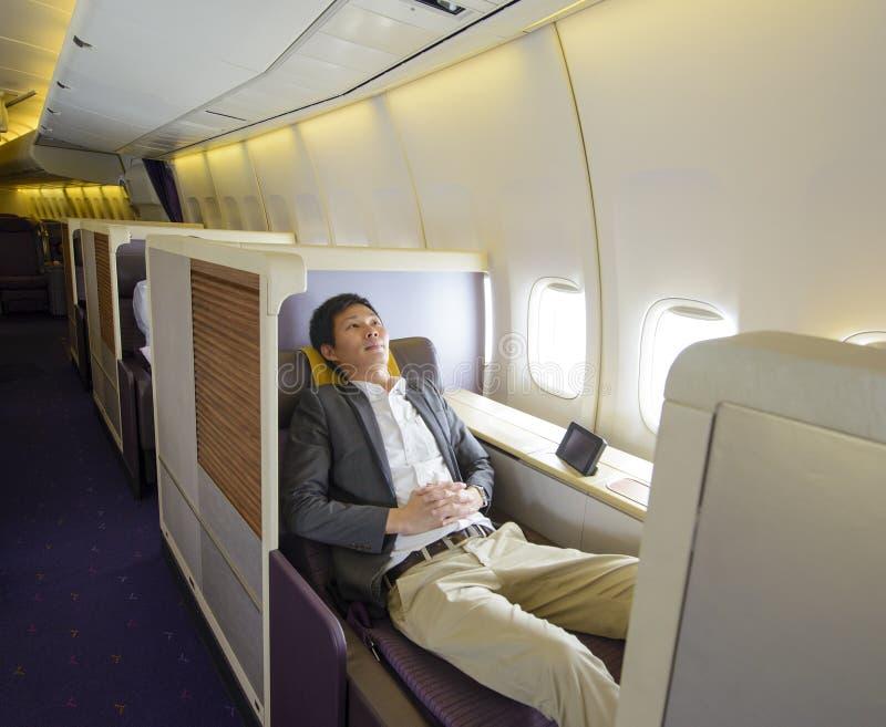 Mediados de hombre de negocios adulto relajado que duerme en asiento de la primera clase foto de archivo libre de regalías