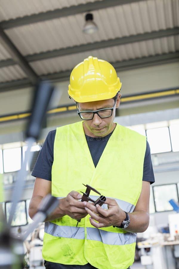 Mediados de metal de medición adulto del trabajador manual con el calibrador en industria imágenes de archivo libres de regalías