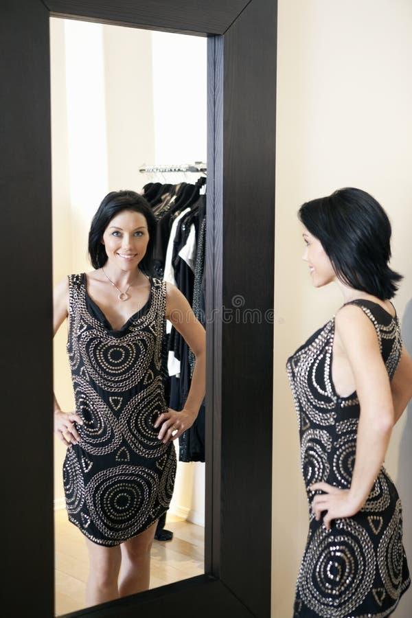 Mediados de mujer adulta feliz que lleva un vestido elegante que se coloca delante del espejo con las manos en caderas en boutique fotos de archivo libres de regalías