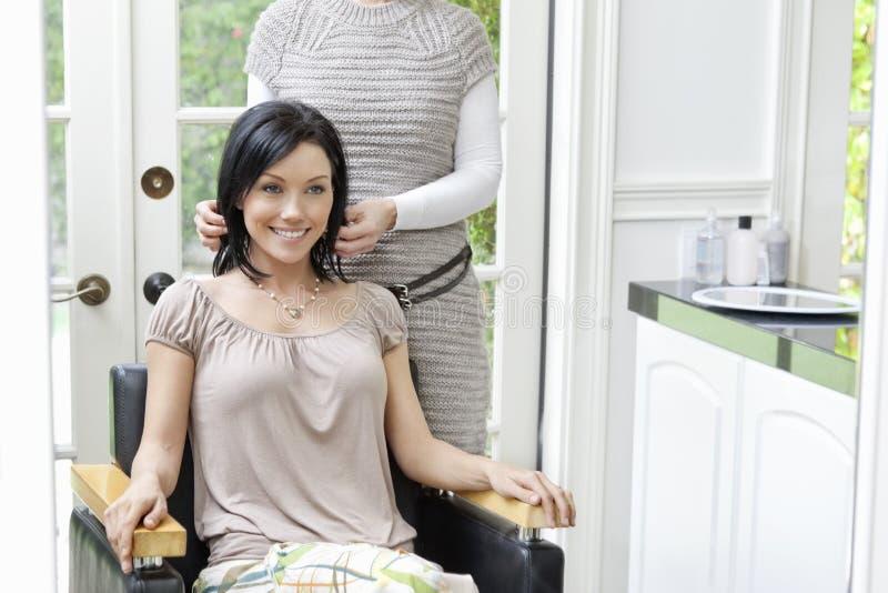 Mediados de mujer adulta hermosa feliz con el peluquero en fondo foto de archivo