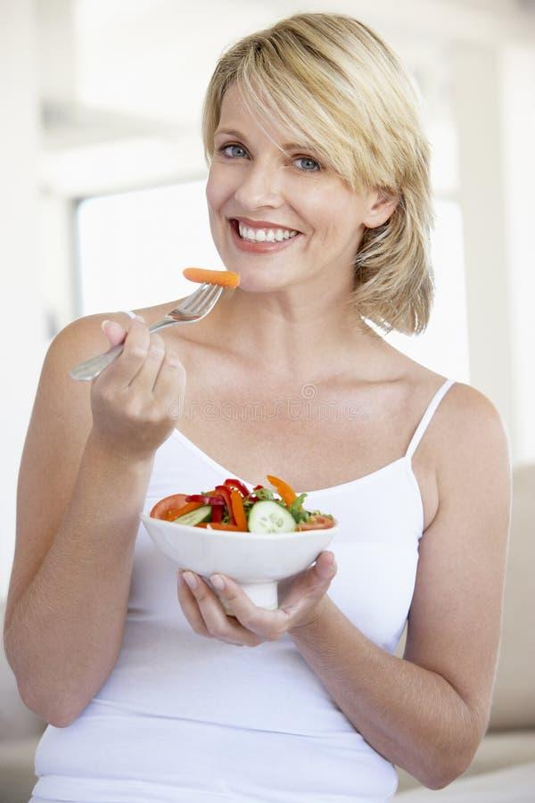 Mediados de mujer adulta que come la ensalada fotos de archivo