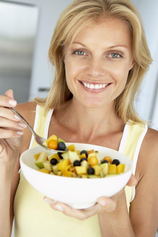 Mediados de mujer adulta que come un tazón de fuente de fruta fresca fotografía de archivo