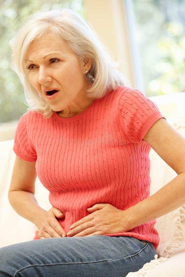 Mediados de mujer de la edad con dolor de estómago foto de archivo