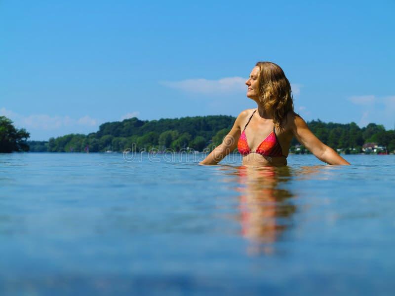 Mediados de mujer de la edad que se relaja en un lago hermoso foto de archivo