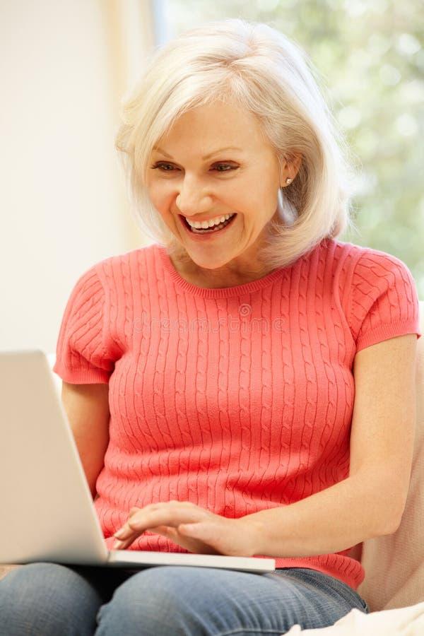 Mediados de mujer de la edad que usa el ordenador portátil en casa imágenes de archivo libres de regalías