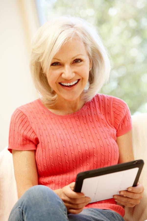 Mediados de mujer de la edad que usa la tableta en casa imágenes de archivo libres de regalías