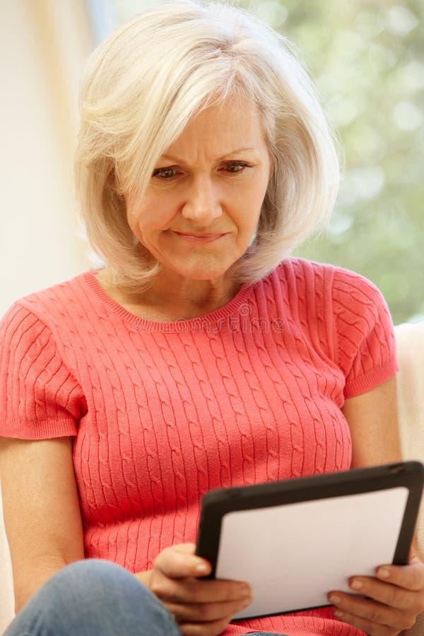 Mediados de mujer de la edad que usa la tableta en casa imagenes de archivo