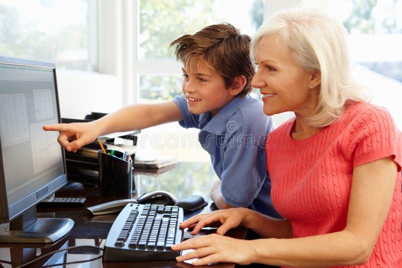 Mediados de mujer y nieto de la edad que usa el ordenador imagen de archivo libre de regalías