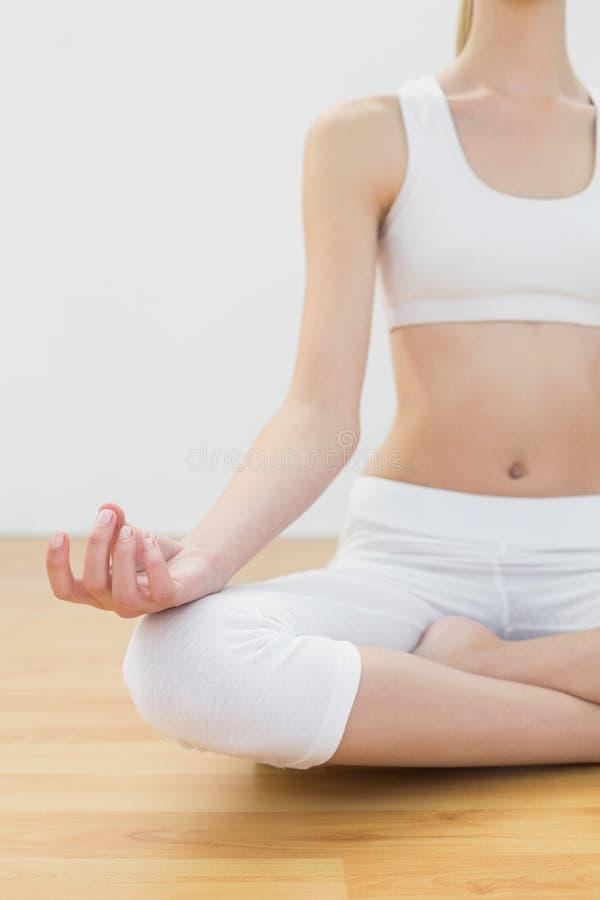Mediados de sección de la mujer delgada del ajuste que medita sentarse en la posición de loto imagen de archivo