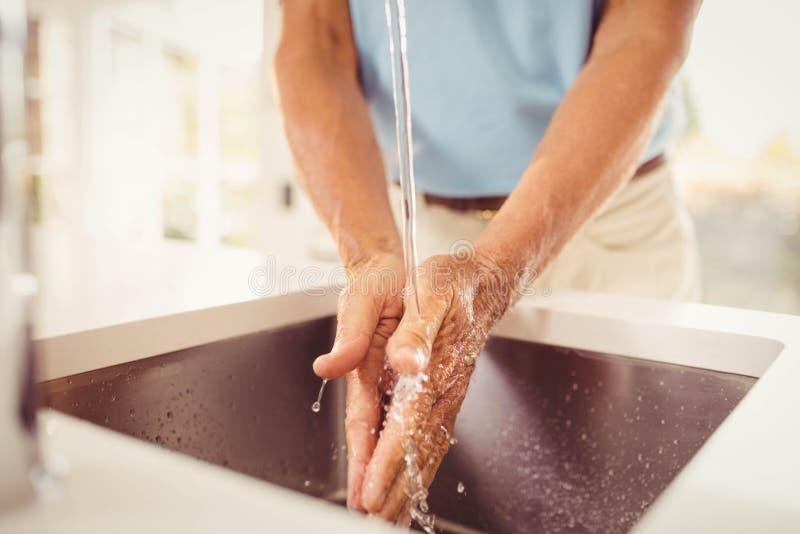 Mediados de sección de las manos que se lavan del hombre mayor fotos de archivo