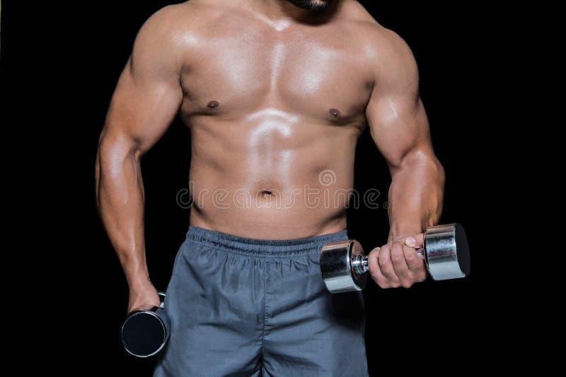 Mediados de sección de un culturista con pesas de gimnasia fotos de archivo