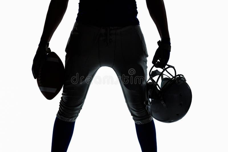 Mediados de sección del deportista de la silueta que sostiene la bola y el casco fotografía de archivo