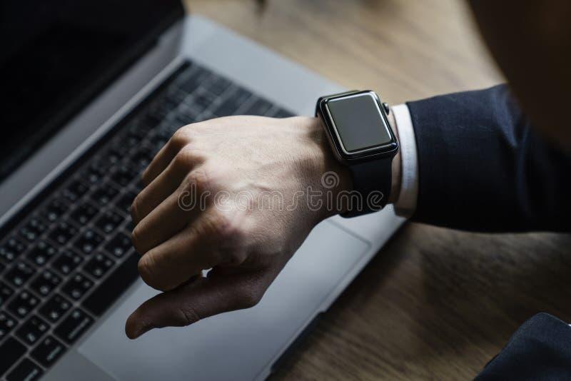 Mediados de sección del ejecutivo de sexo masculino que usa el smartwatch en oficina fotos de archivo