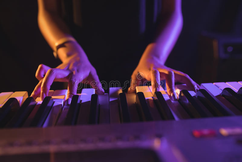 Mediados de sección del músico de sexo femenino que juega el piano imagenes de archivo