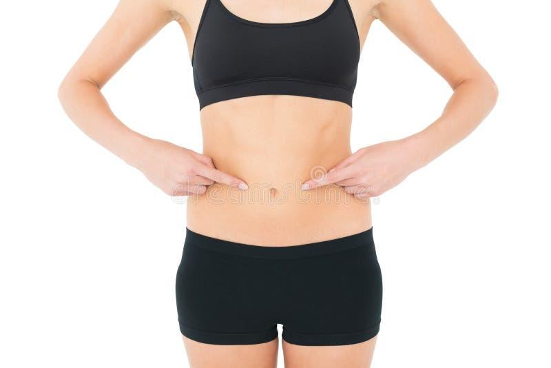 Mediados de sección del primer de una mujer del ajuste con las manos en el estómago foto de archivo libre de regalías