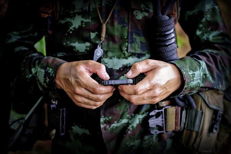 Mediados de sección del soldado militar que usa el teléfono móvil en campo de bota imagen de archivo