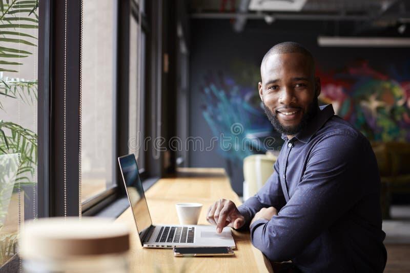 Mediados de sentada creativa masculina negra adulta por la ventana en café usando el ordenador portátil, dando vuelta y sonriendo foto de archivo libre de regalías