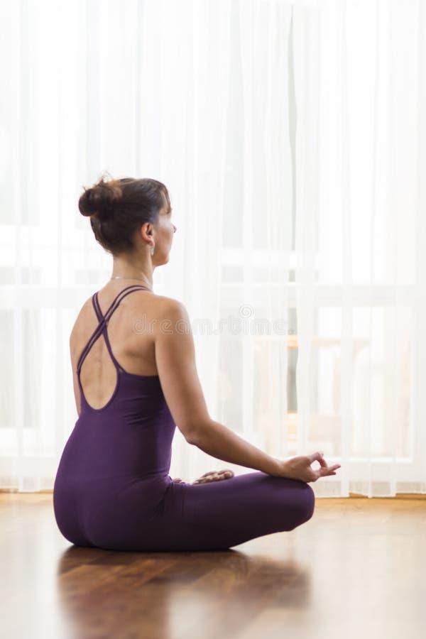 Mediados de yoga practicante envejecida de la mujer caucásica El sentarse en traje púrpura del cuerpo en la ventana de Lotus Pose imágenes de archivo libres de regalías