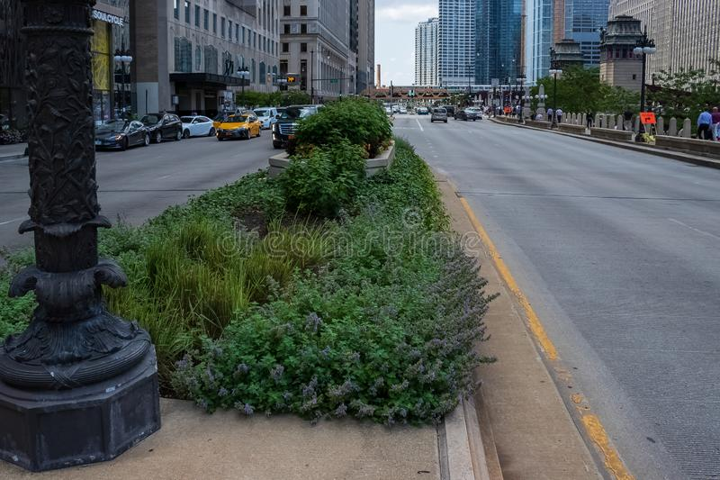 Median in the middle of Wacker Dr. with open space on one side adn traffic on the otherl while pedestrians walk on sidewalk stock photo