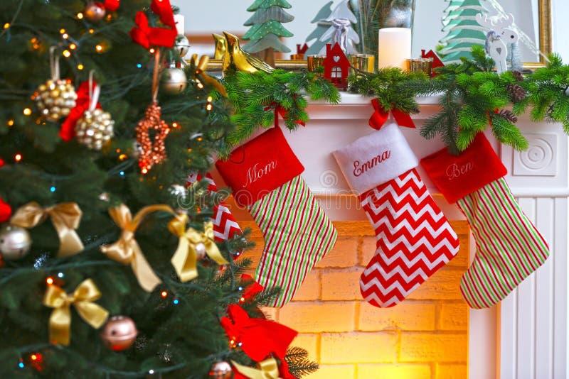 Medias de la Navidad que cuelgan en la chimenea cerca de árbol de abeto, fotografía de archivo libre de regalías