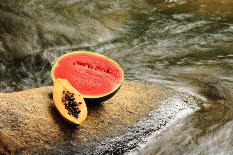 Medias sandía y papaya en las rocas imagenes de archivo