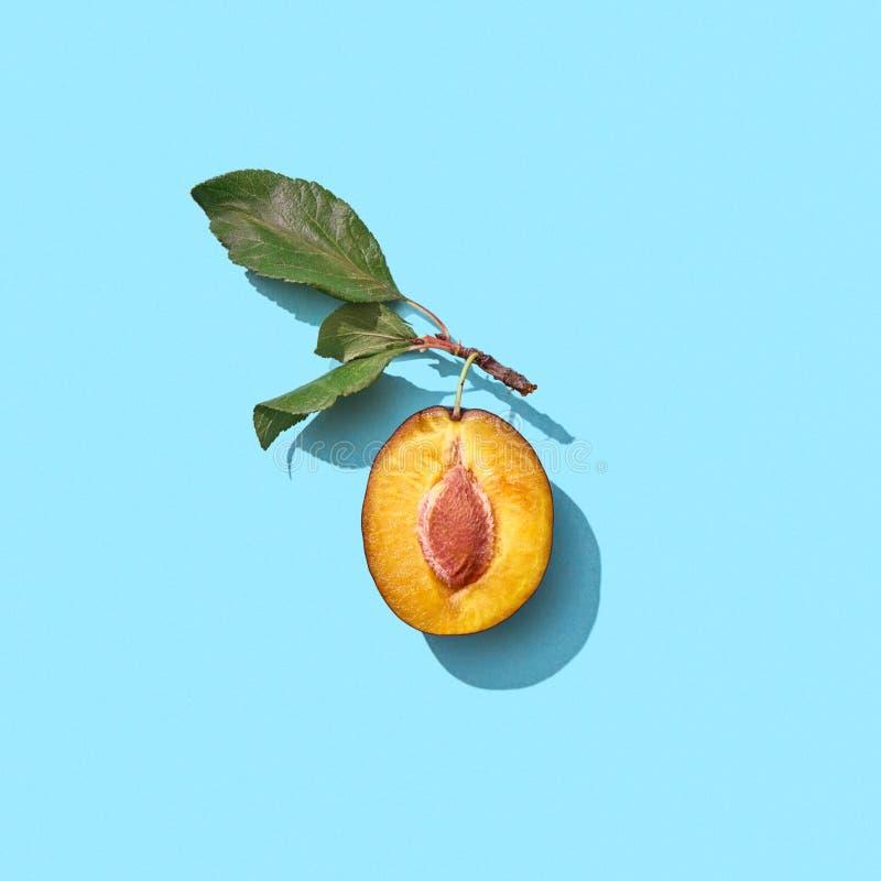 A medias un ciruelo maduro con las hojas verdes en un fondo azul con el espacio de la copia Comida de la vitamina Endecha plana imagen de archivo