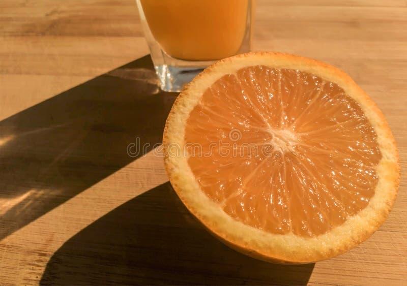 A medias una naranja con el vidrio de zumo de naranja fresco con las sombras foto de archivo