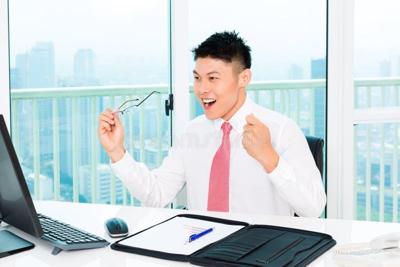 Mediatore asiatico che vende alla borsa valori in ufficio fotografie stock